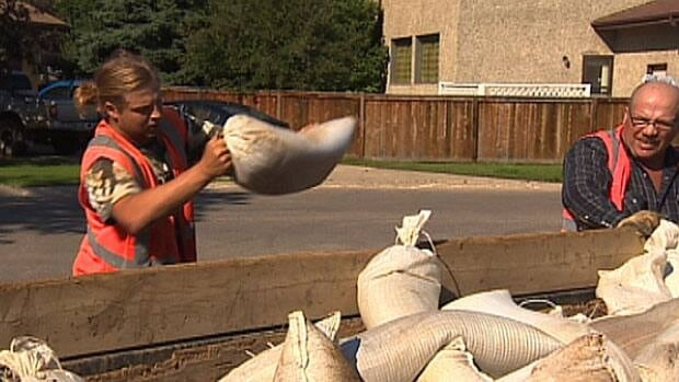 Workers remove sandbags from residential neighbourhoods in Fort McMurray one month after floods chased 400 people from their homes.