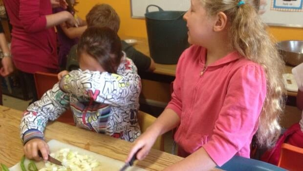 Grade 5 students at Saint Catherine's School hold back tears as they chop onions harvested from the school garden.