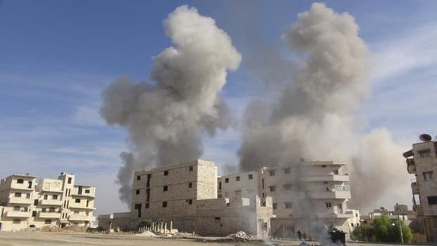 Smoke rises after a Syrian Air Force fighter jet loyal to Syria's President Bashar Assad fired missiles at Marat al-Numan, near the northern province of Idlib on Tuesday.