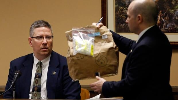 Prosecuting attorney Brian Deckert, right, asks Bureau of Criminal Investigation Special Agent Ed Lulla about an evidence bag containing a blanket in an Ohio courtroom earlier this week.