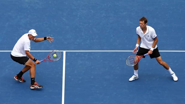 Daniel Nestor, right, and Vasek Pospisil of Canada in action during their men's doubles match against Bob and Mike Bryan on September 1, 2013.