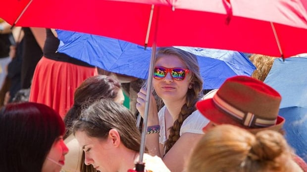 A young woman waiting to audition for the role of Dorothy as part of CBC Television's reality series Over the Rainbow enjoys some shade in downtown Toronto on Monday.