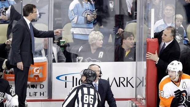 Pittsburgh Penguins assistant coach Tony Granato, left, stands on the boards between benches to talk with Philadelphia Flyers assistant coach Craig Berube, top right, during a on-ice fight during the third period in Pittsburgh on Sunday.