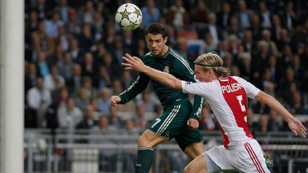 Real Madrid player Cristiano Ronaldo, rear, heads as Ajax goalkeeper Kenneth Vermeer, left, and player Christian Poulsen, right, try to defend Wednesday in Amsterdam.