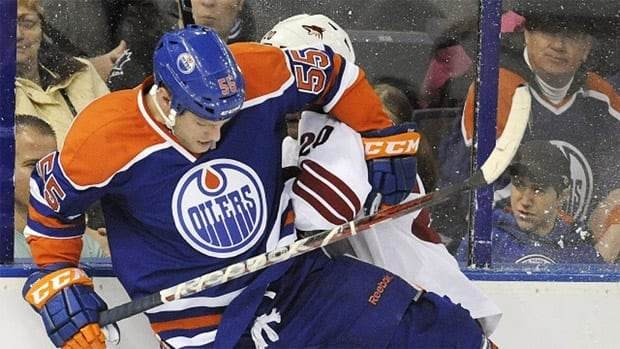 Edmonton Oilers' Ben Eager, left, checks Phoenix Coyotes Chris Summers during the first period of the NHL hockey game in Edmonton on Saturday, February 25, 2012.