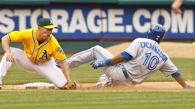 Blue Jays' Edwin Encarnacion steals third base in front of Athletics third baseman Brandon Inge in the 11th inning. Encarnacion scored on the play on Oakland catcher George Kottaras's error.