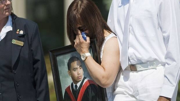 The mother of during shooting victim Joshua Yasay carries his photo at his funeral service in Ajax, Ont. on Monday.