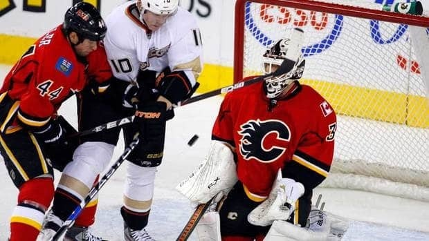 Anaheim Ducks' Corey Perry, centre, and Calgary Flames' Chris Butler jostle in front of goalie Miikka Kiprusoff during first period Thursday.