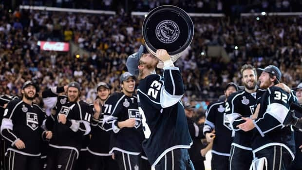 Los Angeles Kings captain Dustin Brown (23) kisses the Stanley Cup after the Kings beat the New Jersey Devils 6-1 during Game 6 of the Stanley Cup final on Monday in Los Angeles.