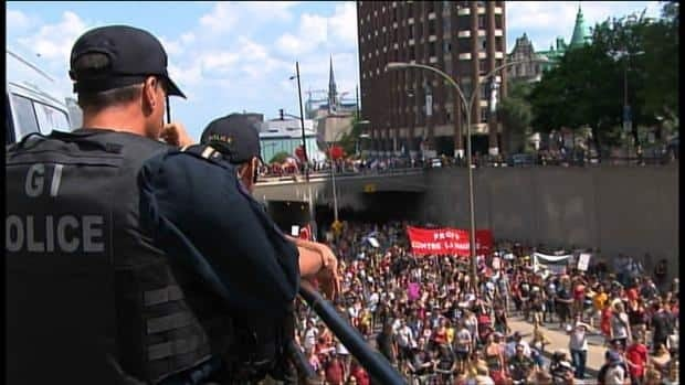 Montreal police watch as protesters march up Berri Street on July 22.