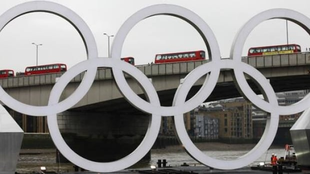 A barge with the Olympic rings floats below London Bridge as a line of double decker buses cross it during a promotional event for the London 2012 Olympic Games, on the Thames in London, Feb. 28.