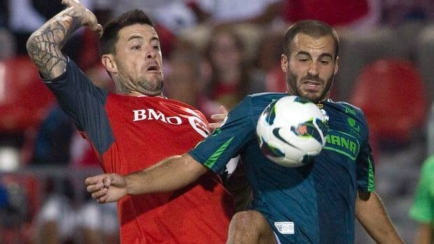 Toronto FC's Eric Hassli, left, battles for the ball with Santos Laguna's Marc Crosas in Toronto on Tuesday August 28, 2012.