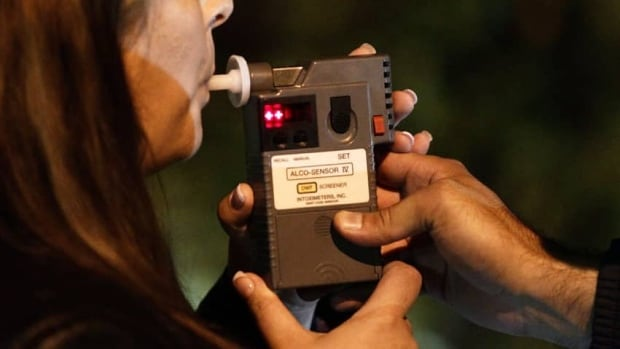 An RCMP officer performs a breathalyzer on a driver during a roadside check in Surrey, B.C., just before midnight in 2010. MADD Canada is calling for police officers to also conduct saliva tests to check if a driver is on drugs.