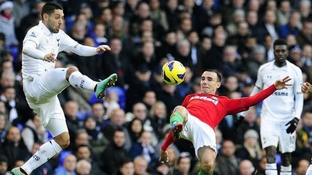 Swansea's Leon Britton, right, vies with Tottenham Hotspur's Clint Dempsey during the match at White Hart Lane in London, England on December 16, 2012.