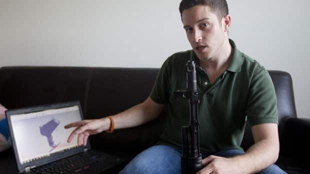 In this Oct. 3, 2012 photo, Wiki Weapons project leader Cody Wilson points to his laptop screen displaying an image of a prototype plastic gun on the screen in Austin, Texas.