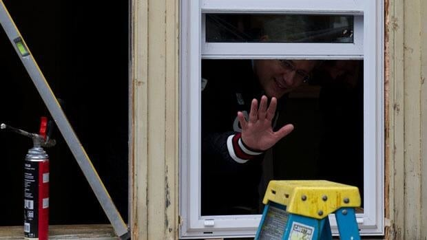Prime Minister Stephen Harper waves to reporters last spring while announcing the popular ecoENERGY home retrofit program would be brought back for one year.
