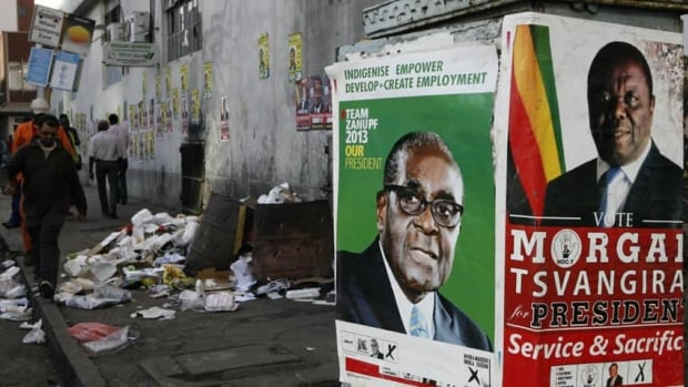 Election campaign posters are pictured near Zimbabweans walking on a street blocked by uncollected garbage in Harare. President Robert Mugabe is seeking re-election after 33 years as leader of the now economically struggling nation.