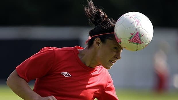 Canada's Melissa Tancredi, heads the ball during a women's soccer training session for the 2012 London Summer Olympics, in Coventry, England.