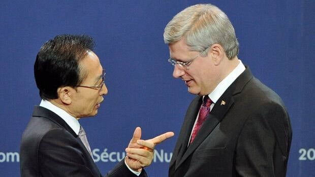 South Korea's President Lee Myung-bak, left, welcomes Canada's Prime Minister Stephen Harper as he arrives at the Nuclear Security Summit in Seoul Monday.