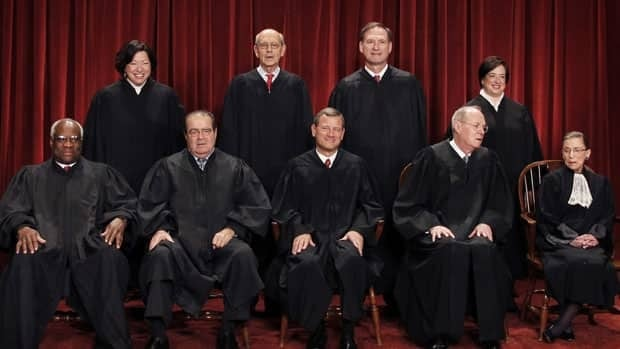 The nine justices: Seated - Ruth Bader Ginsburg, right, Anthony Kennedy, Chief Justice John Roberts, center, Antonin Scalia, Clarence Thomas. Standing from left are Sonia Sotomayor, Stephen Breyer, Samuel Alito Jr., and Elena Kagan.