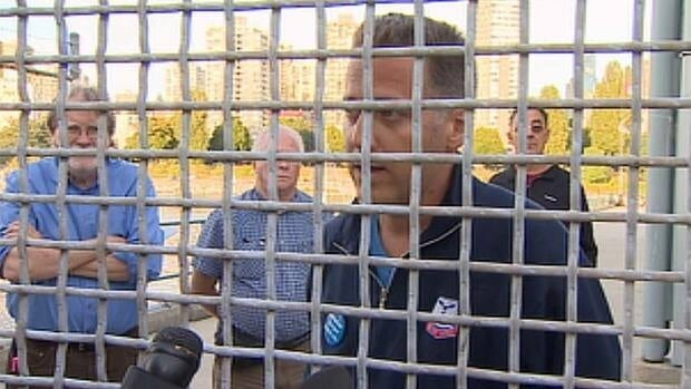 Union official Dave Clark speaks to the media through the fence at Vancouver's Kitsilano Coast Guard Station.