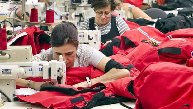 Workers piece together outerwear on the manufacturing floor of Canada Goose's facility in Toronto. Average weekly earnings increased by 0.5 per cent last month.