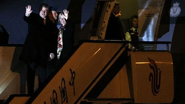 Canadian Prime Minister Stephen Harper, left, and his wife Laureen Harper wave as they arrive at Capital International Airport in Beijing Tuesday, Feb. 7, 2012.
