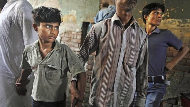 Workers from Bachpan Bachao Andolan, or Save the Childhood Movement, remove a bonded child laborer after a raid at a factory in New Delhi, India, Tuesday.