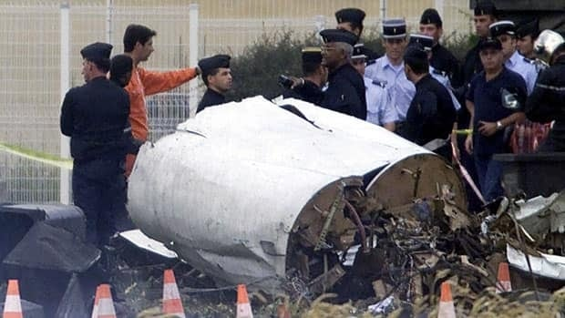 Rescue workers stand on the crash site of an Air France Concorde plane on July 25, 2000. The plane crashed in Gonesse, outside Paris, shortly after take off. A French appeals court decided on Thursday to overturn manslaughter convictions against Continental Airlines and a mechanic for the July 2000 crash.