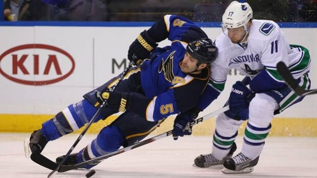 Canucks forward Ryan Kesler upends defenceman Barret Jackman (5) in a 3-2 loss to the Blues at Scottrade Center on Nov. 4.