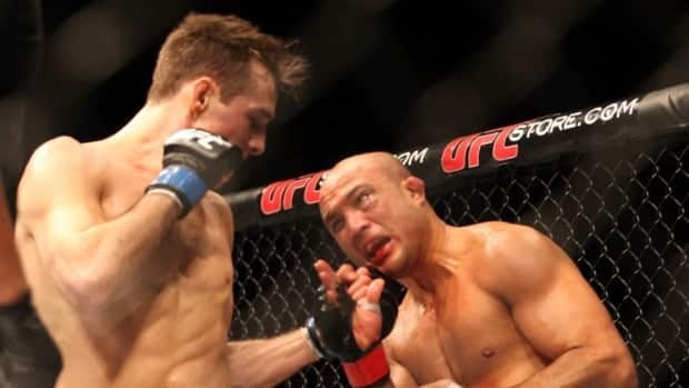BJ Penn, right, takes a punch from Canadian Rory MacDonald during their UFC bout in Seattle, Saturday, Dec. 8, 2012. MacDonald won via unanimous decision.