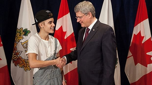 A meeting with pop star Justin Bieber, left, helped to push Prime Minister Stephen Harper's Google search rankings to the top of the heap for Canadian politicians in 2012.