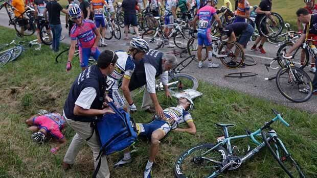 Grega Bole of Slovenia, standing left, points to his teammate Davide Vigano of Italy, while doctors tend to Wouter Poels of The Netherlands after a crash during the sixth stage of the Tour de France.