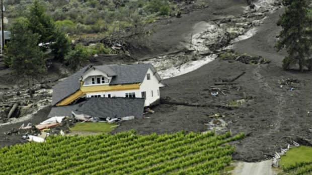 A house is damaged by a landslide as water continues to rush down the mountain near Oliver, B.C. in June, 2010.