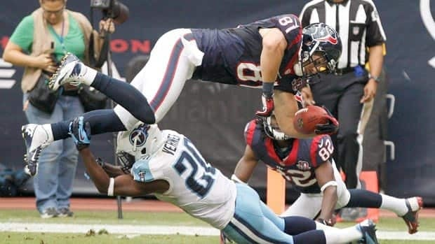 Owen Daniels of the Houston Texans goes over Alterraun Verner of the Tennessee Titans for a touchdown reception Sunday at Reliant Stadium.