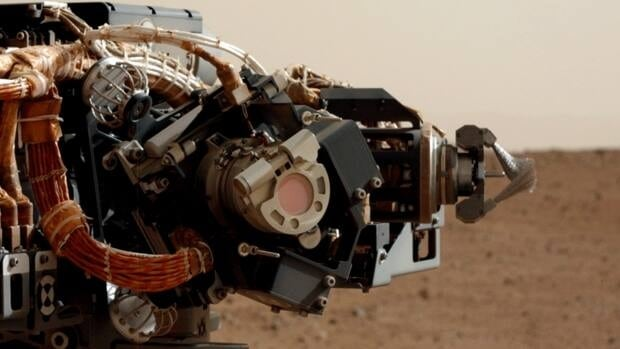 A close-up of the Mars Hand Lens Imager (MAHLI), a camera that is one of several tools on a turret at the end of the Curiosity rover's robotic arm. The reddish circle is the camera's dust cover, which has a coating of red Martian dust on it that was kicked up during landing. The image was taken by the rover's mast camera.