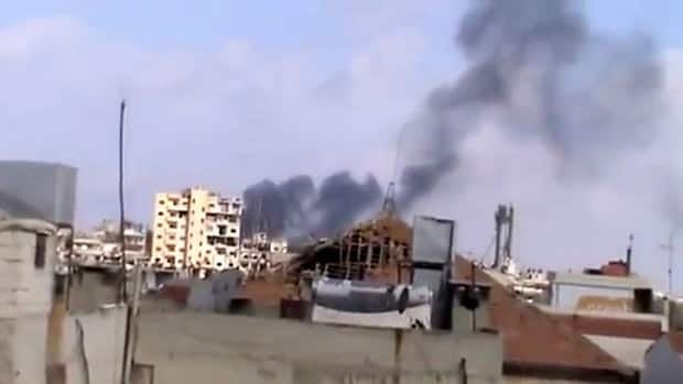 Smoke rises from houses due to government shelling in Homs on Friday.