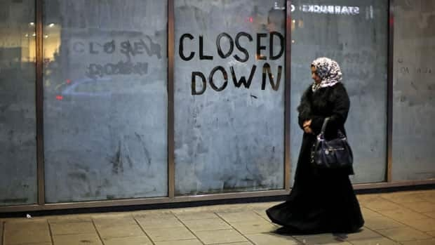 A woman passes a closed down business in central London on Thursday. The European Central Bank sees weak economic activity extending into next year.