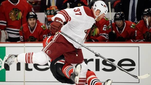 Coyotes forward Raffi Torres, front, takes out Blackhawks winger Marian Hossa, back, during Game 3 of their first-round playoff series on Tuesday.