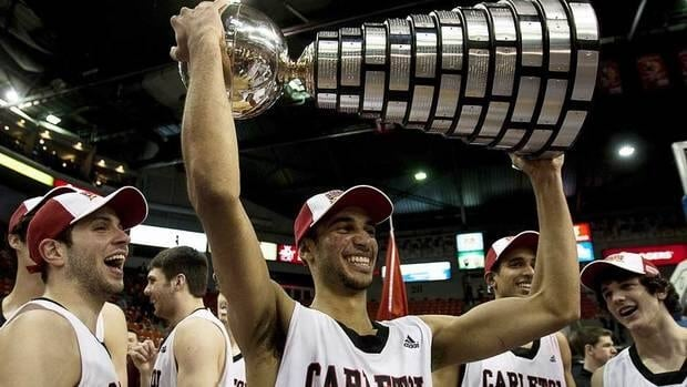 Carleton Ravens Philip Scrubb, tournament MVP, raises the W. P. McGee trophy after defeating the University of Alberta Golden Bears 86-67 in the CIS Final 8 men's basketball championship game in Halifax on Sunday.