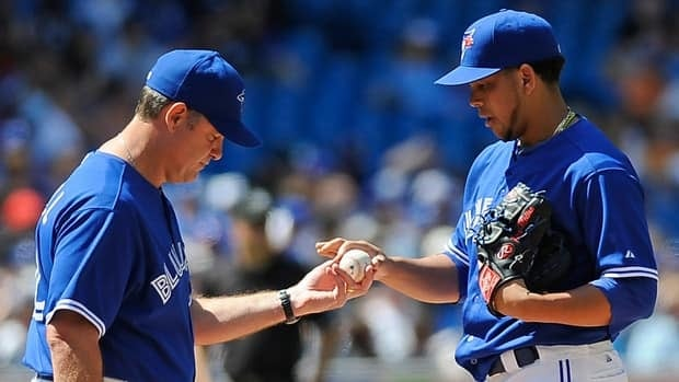 Manager John Farrell of the Toronto Blue Jays, left, takes the ball from Henderson Alvarez during the game against the Texas Rangers.