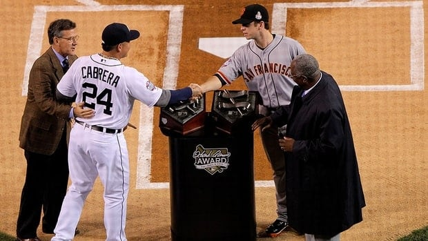 Miguel Cabrera, second from left, of the Detroit Tigers, shakes hands with Buster Posey, second from right, of the San Francisco Giants, after being selected as the winners of the 2012 Hank Aaron Award before a 2012 World Series game. The duo have also now claimed their respective league MVP awards.