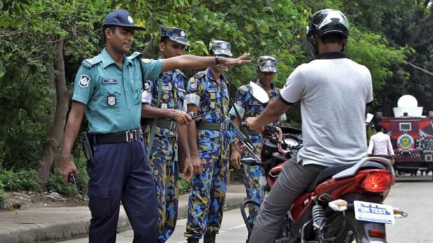 Police stop a motorist in front of the U.S. embassy building that remained closed due to security threat in Bangladesh, one of several countries where U.S. diplomatic posts will be closed this week.