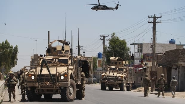 U.S. soldiers secure a street as a medevac helicopter flies in sky during an attack at the governor's compound in Kandahar, Afghanistan, on Saturday that left two policemen and two attackers dead.