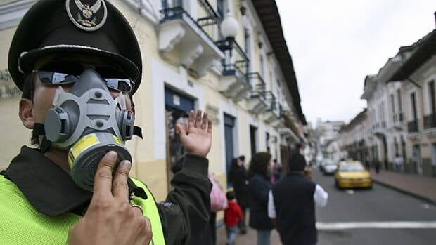 An Ecuadorean police officer guides traffic as he covers his face with a mask due to air pollution, which has been linked to heart attacks.