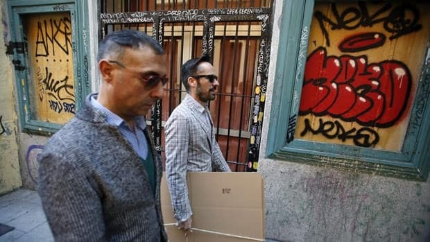 Men walk past a closed-down business in downtown Madrid last month.