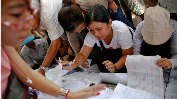 People try to find their names on the voters' lists at a polling station in Phnom Penh on Sunday.