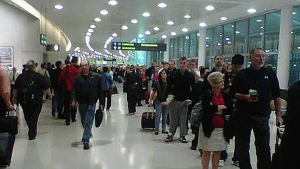 Travellers line up at Toronto's Pearson International Airport on Tuesday morning.