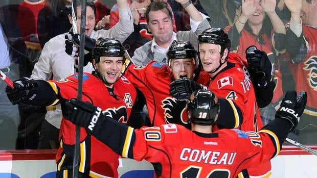 Calgary Flames' Matt Stajan, centre, celebrates his overtime goal with teammates Mark Giordano, left, Jay Bouwmeester, right, and Blake Comeau (10) against the San Jose Sharks in Calgary on Tuesday.