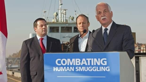 Minister of Public Safety Vic Toews, right, Minister of Citizenship, Immigration and Multiculturalism Jason Kenney, far left, and former minister for the Asia-Pacific Gateway Stockwell Day announce a series of reforms to combat human smuggling in Delta, B.C., on Oct. 21, 2010. The freighter MV Ocean Lady, which was seized off the B.C. coast in 2009 with 76 illegal Tamil migrants aboard sits dockside behind them.
